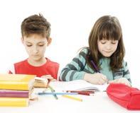 Jonge meisje en jongen die thuiswerk doen stock afbeelding