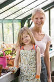 Jonge meisje en vrouw in serre het glimlachen Stock Afbeelding