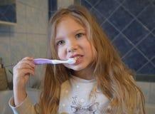 Jonge meisje het borstelen tanden vóór kleuterschool royalty-vrije stock afbeeldingen