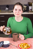 Jonge meisje het drinken thee bij keuken Stock Foto's