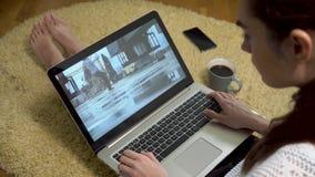 Jonge meisje het letten op straat het dansen video die laptop het scherm met behulp van terwijl het zitten thuis op het tapijt stock videobeelden