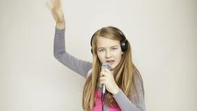 Jonge meisje het luisteren muziek die op hoofdtelefoons microfoon houden, het zingen en het funy dansen stock video