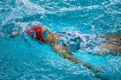 Jonge meisje het zwemmen rugslag in pool Stock Afbeeldingen