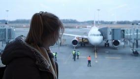 Jonge meisje of tiener die glazen, in een sjaal dragen die een vliegtuig die bij de luchthaven bekijken, haar paspoort en kaartje stock video