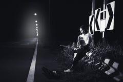 jonge meisje zitting en het spelen gitaar aan wegkant met verkeerstekenachtergrond stock afbeeldingen