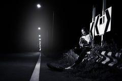 jonge meisje zitting en het spelen gitaar aan wegkant met verkeerstekenachtergrond royalty-vrije stock afbeeldingen