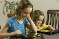 Jonge meisjes bij lijst die thuiswerk op horizontale tabletten doen, Stock Foto