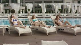 Jonge meisjes die bij de pool ontspannen stock footage