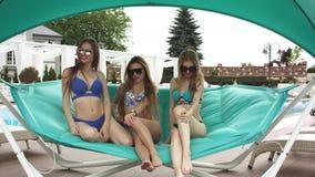 Jonge meisjes die bij de pool ontspannen stock videobeelden
