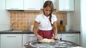 Jonge meisjes die deeg op donkere lijst in keuken kneden stock videobeelden