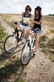 Jonge meisjes die een fiets berijden Stock Foto's