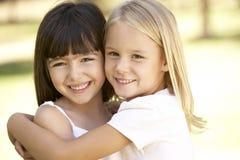 2 jonge Meisjes die elkaar Omhelzing geven Royalty-vrije Stock Foto's