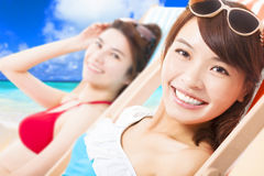 Jonge meisjes die en op een ligstoel zonnebaden liggen Stock Foto's