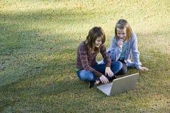Jonge meisjes die laptop op gras met behulp van Royalty-vrije Stock Foto's