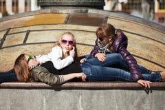Jonge meisjes die op de stadsstraat ontspannen Stock Foto's