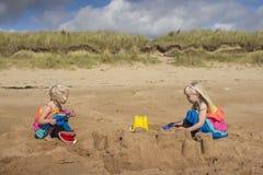 Jonge meisjes die op het strand op een de zomersdag spelen stock foto's
