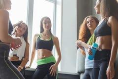 Jonge meisjes die in sportkleding vóór yogaklasse babbelen stock afbeeldingen