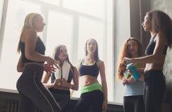 Jonge meisjes die in sportkleding vóór yogaklasse babbelen stock afbeelding