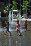 Jonge meisjes die in stedelijke fontein spelen om hitte te slaan Royalty-vrije Stock Foto