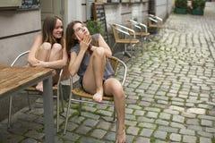 Jonge meisjes die terwijl het zitten in een straatkoffie roddelen De zomer Stock Afbeeldingen