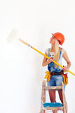 Jonge meisjes kleurende muur met rol, terwijl status op ladder stock foto's