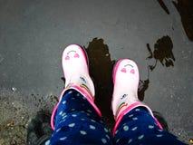 Jonge meisjes met roze laarzen met zijn vader die pret buiten in straat na regen hebben stock fotografie