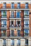 Jonge meisjes op balkons van een typische de bouwvoorgevel op een stree Royalty-vrije Stock Afbeeldingen