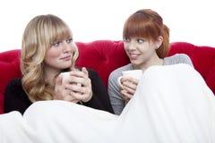 Jonge meisjes op bank met koffie Stock Afbeelding