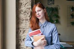 Jonge meisjes vrouwelijke student met het lange rode haar stellen voor een portra royalty-vrije stock afbeeldingen
