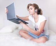 Jonge meisjes witn zilveren laptop en skype hoofdtelefoon Royalty-vrije Stock Afbeelding