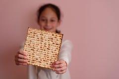 Jonge meisjesholding matzah of matza Joodse de uitnodiging of de groetkaart van de vakantiepascha Selectieve nadruk De ruimte van royalty-vrije stock afbeeldingen