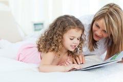 Jonge meisjeslezing met haar grootmoeder stock foto's