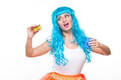 Jonge meisjespop met blauw haar plastiek die een sandwich eten honger royalty-vrije stock foto's