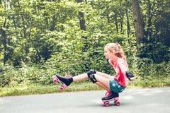 Jonge meisjesrol die neer op een bosweg schaatsen Royalty-vrije Stock Foto's