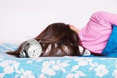 Jonge meisjesslaap terwijl de klok belt stock foto's