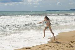 Jonge meisjesspelen op strand II Royalty-vrije Stock Afbeeldingen