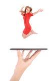Jonge meisjessprong die tabletpc op mensenhand met behulp van Royalty-vrije Stock Afbeeldingen