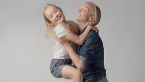 Jonge meisjessprongen op handen aan mum en het glimlachen van allebei stock video