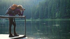 Jonge meisjeswandelaar met rugzak die foto van bosmeer nemen stock footage