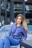 Jonge meisjeszitting als voorzitter met de bouw van achtergrond Royalty-vrije Stock Afbeelding