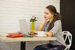 Jonge meisjeszitting bij lijst en het onderzoeken van laptop monitor met kop van drank Royalty-vrije Stock Foto