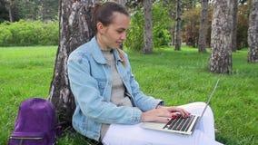Jonge meisjeszitting buiten de bureaubouw die aan laptop werken stock videobeelden
