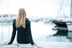 Jonge meisjeszitting in de haven Stock Fotografie