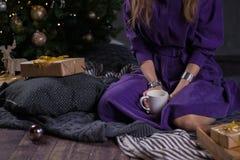 Jonge meisjeszitting dichtbij de Kerstboom met giften en het drinken koffie van een witte kop vaas toe stock fotografie