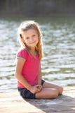Jonge meisjeszitting door meer Stock Foto