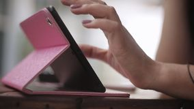 Jonge meisjeszitting in koffie bij lijst en gebruik een tabletcomputer Het proces van spijkers stock footage