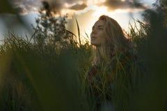 Jonge meisjeszitting in lang gras bij backlit zonsondergang royalty-vrije stock fotografie