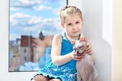 Jonge meisjeszitting met kat op venster Stock Foto's