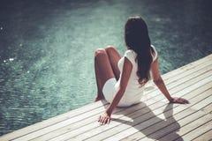 Jonge meisjeszitting naast een zwembad stock foto's