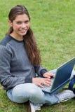Jonge meisjeszitting neer terwijl het gebruiken van haar laptop Royalty-vrije Stock Afbeelding